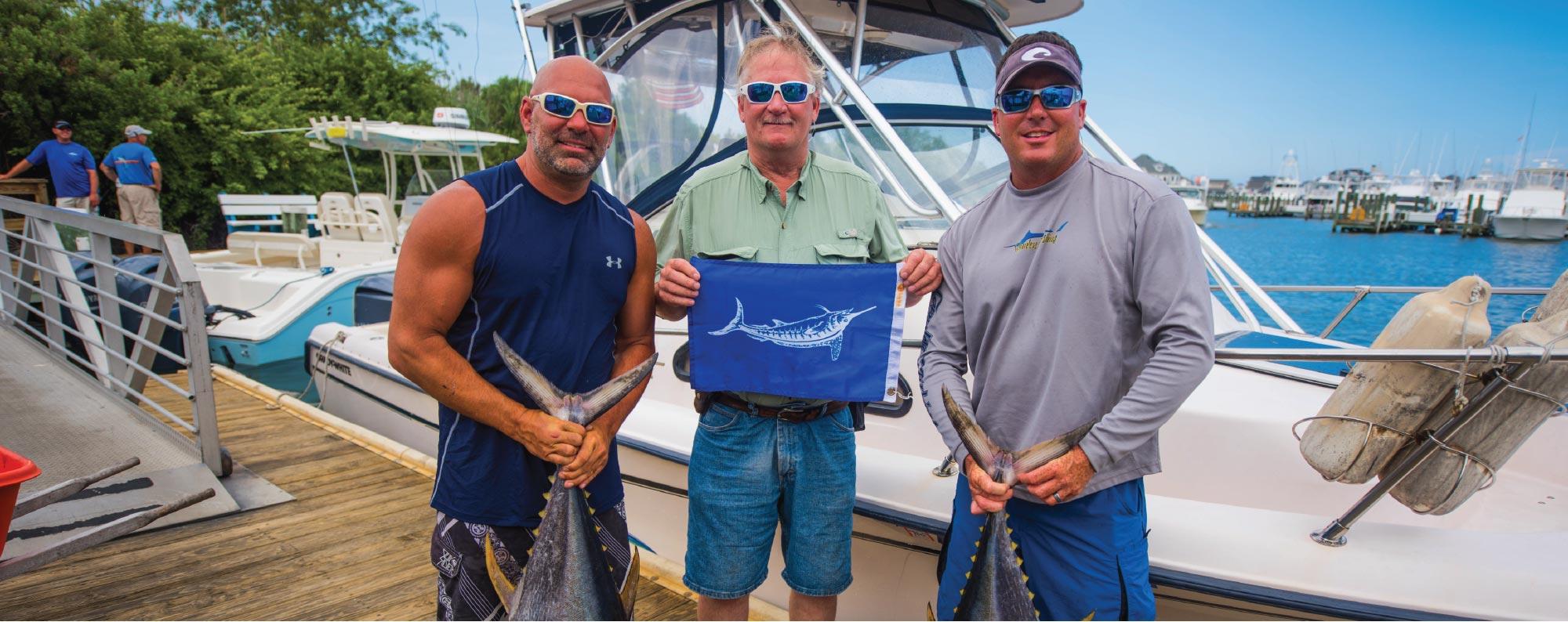 Three men with Tuna and Marlin flag