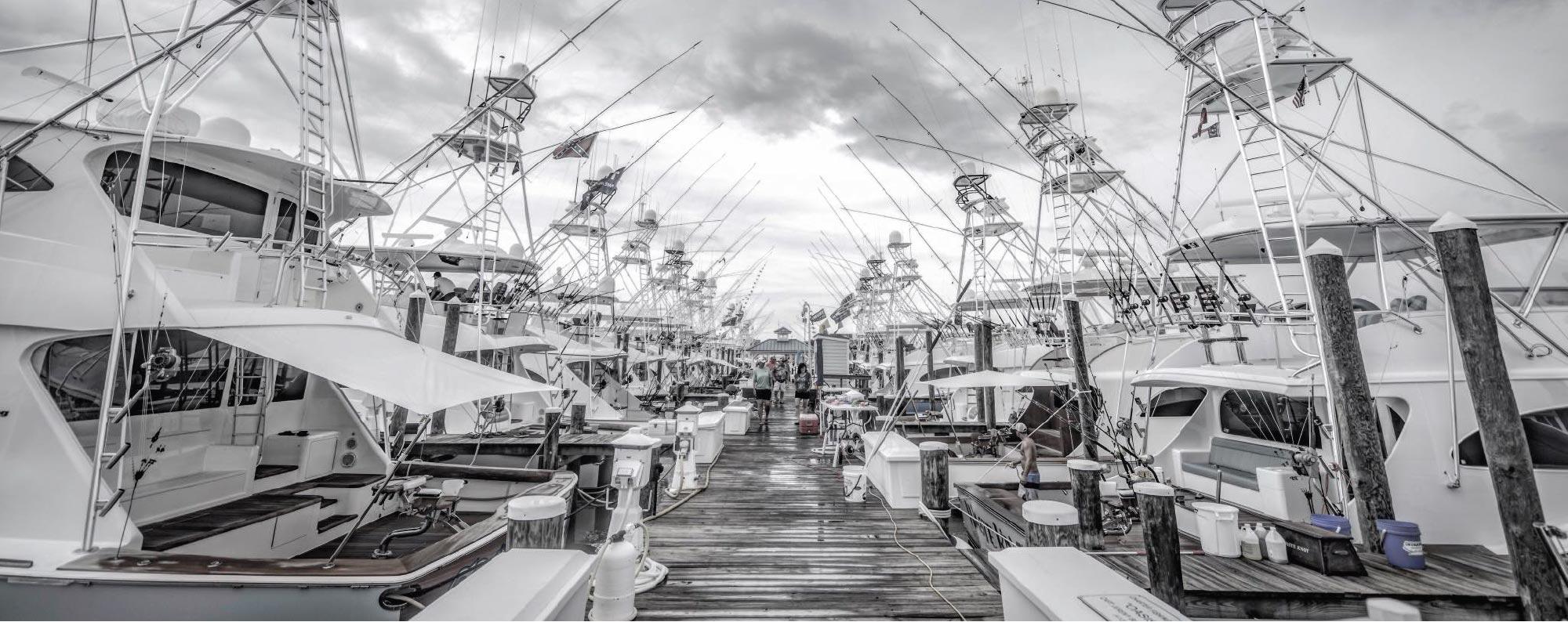 Greyscale Marina dock full of fishing boats