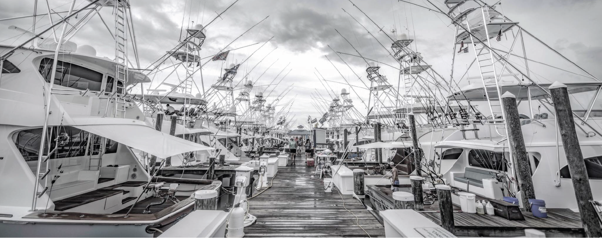 Greyscale Marina dock full of fishing boats